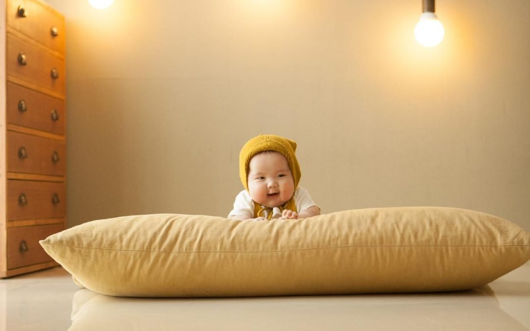 baby on yellow pillow - Petite Dreamers