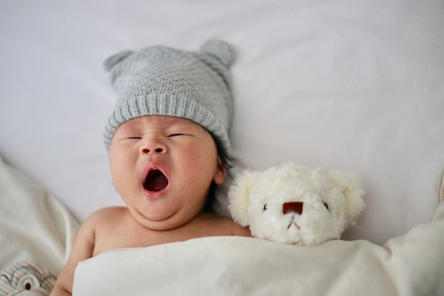 Baby with hat yawning - Petite Dreamers