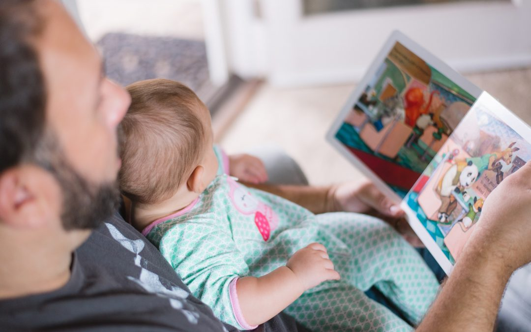 man reading to baby - Petite Dreamers